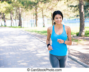 Smiling woman running in park - Smiling sporty woman running...