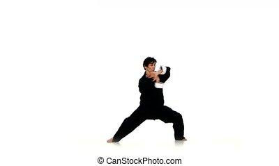 A karate or wushu boy in a black kimono on a white