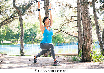 Young woman stretching outdoors in park - Young sporty woman...
