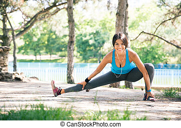 Sporty woman doing stretching exercise in park