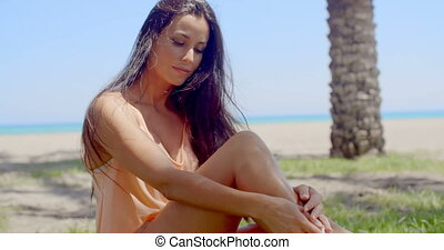 Pensive Lady Sitting on Grassy Ground at the Beach - Close...