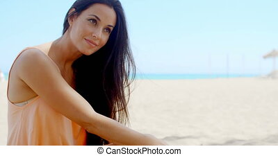 Attractive Young Lady Relaxing at the Beach Sand