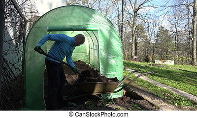 gardener compost barrow - Gardener man with fork unload...