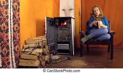 woman read book stove - Attractive young woman relaxing in...