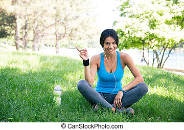 Happy fitness woman sitting on the green grass outdoors in...