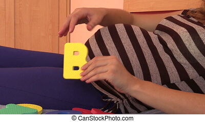 woman expecting boy - Closeup of pregnant woman hand pick...