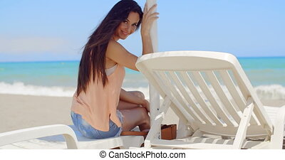 Smiling Pretty Woman Sitting on Beach Sun Lounger