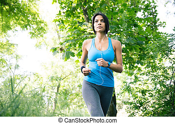 Attractive young woman running in park - Attractive young...