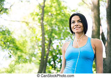 Smiling sports woman in headphones outdoors. looking away