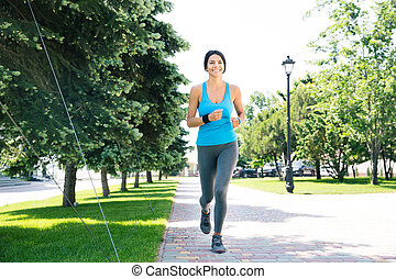 Happy sports woman running outdoors - Full length portrait...