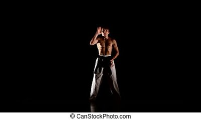 Man training karate or taekwondo Isolated on Black...