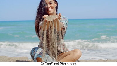 Pretty Lady Sitting at the Beach Holding Sand