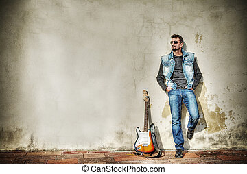 man and guitar against a grungy wall in hdr - man and guitar...
