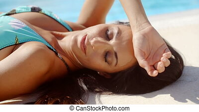 Thoughtful Woman Lying Down at the Poolside - Close up...