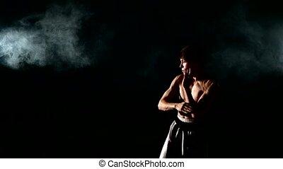 kung-fu  or karate man with naked torso practicing kung fu kicks