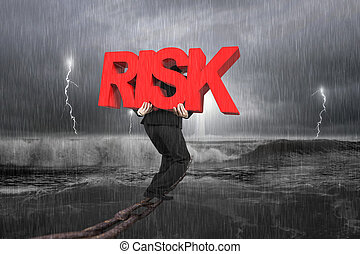 Man carrying red RISK word on chain with stormy ocean - Man...