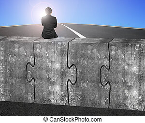 Business man sitting on four huge concrete puzzles connected...