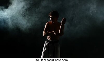 Karate or taekwondo training man punches smoke, close up -...