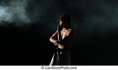 Karate or taekwondo training man punches smoke, close up, Slow motion