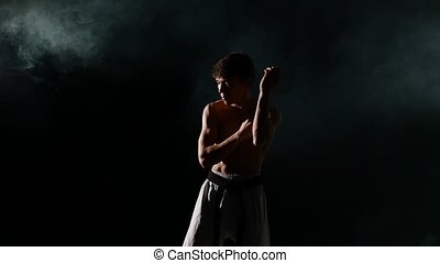 Karate or taekwondo training man punches smoke, close up...