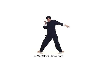 Wushu or karate man in sportswear performing a kick. Martial arts, Slow motion