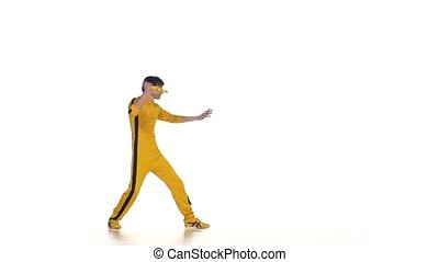 Man in yellow suit training karate and expertly twirling nunchaku, Slow motion