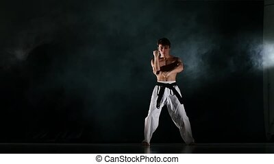 Man training taekwondo or karate Isolated on Black...