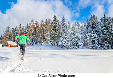 Young man with green jacket running in deep snow