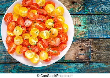 Cuted yellow and red cherry tomatoes in a bowl on old table