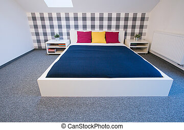 Enormous double bed with colorful sheet in modern bedroom