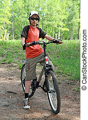 The teenager in a wood on a bicycle