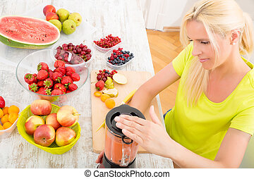 Mature woman blending a smoothie - A blond mature woman...