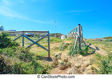 wooden fence by Capo Testa shore on a clear day