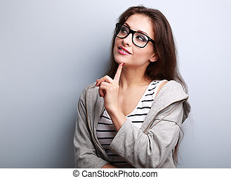 Beautiful young casual woman in glasses thinking about on...