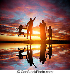 family on a background of the magnificent sunset - happy...