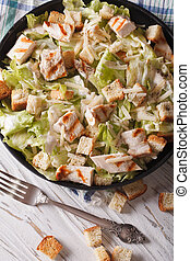 Caesar salad with grilled chicken. Vertical top view closeup