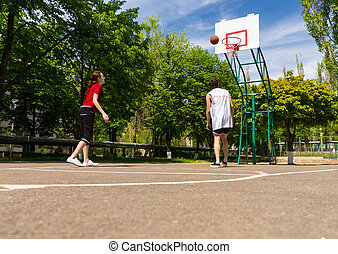Couple Playing Basketball on Outdoor Court