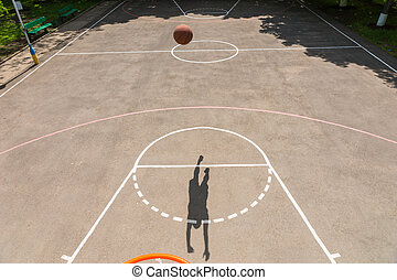 Shadow of Young Man Making Shot on Basketball Ne