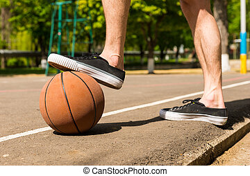 Close Up of Man with Foot on Basketball on Court