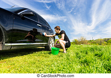 Man with Bucket Washing Black Car in Field - Man with Green...