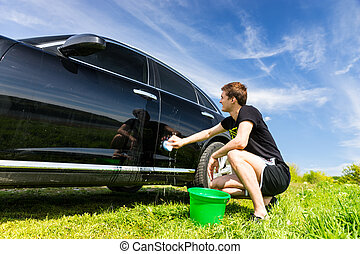 Man Washing Car in Field on Sunny Day - Man Washing Car with...
