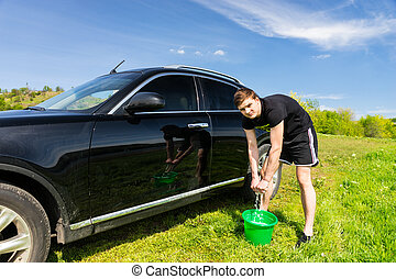 Man Washing Car Using Sponge and Bucket in Field - Man...