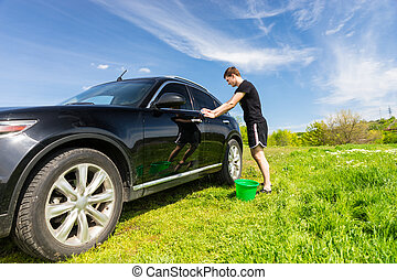 Man with Green Bucket Washing Car in Green Field - Young Man...