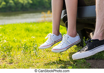 Couple Wearing Sneakers Sitting on Tailgate of Car - Close...