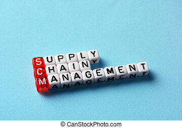 SCM Supply Chain Management written on dices on blue...