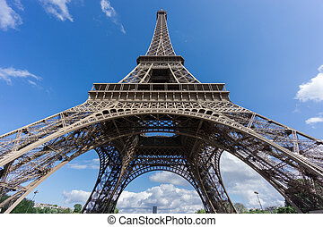 The Eiffel Tower and Montparnasse tower over blue sky -...