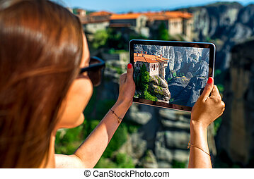 Woman photographing Meteora monastery in Greece
