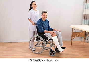 Doctor With Disabled Patient On Wheelchair - Nurse Assisting...
