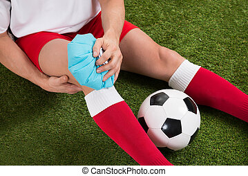 Soccer Player Icing Knee With Ice Pack - Close-up Of A...