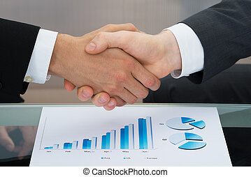 Businessmen Shaking Hand In Front Of Graph - Close-up Of Two...